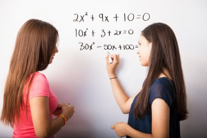 Cute young high school students solving some algebra equations on a white board
